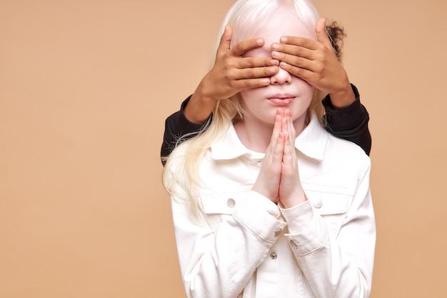 Ragazzo africano chiudere gli occhi di ragazze albine dal retro