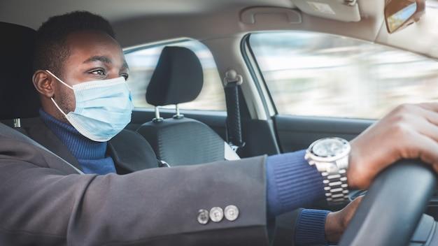 Uomo d'affari africano alla guida di un'auto con maschera medica per protezione corona virus o covid-19