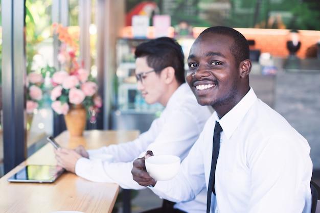 Uomo africano di affari che tiene una tazza di caffè con gli amici asiatici
