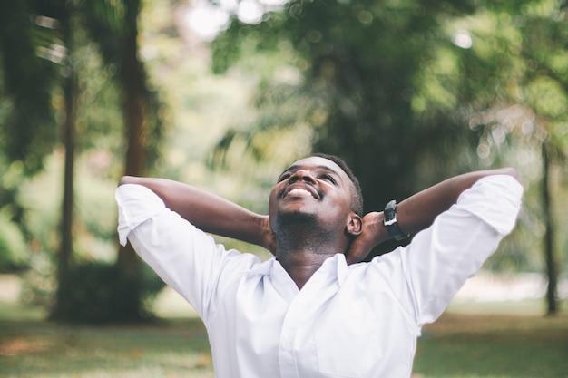 Sorriso dell'uomo d'affari africano e in piedi sulla natura verde con le mani sopra la testa