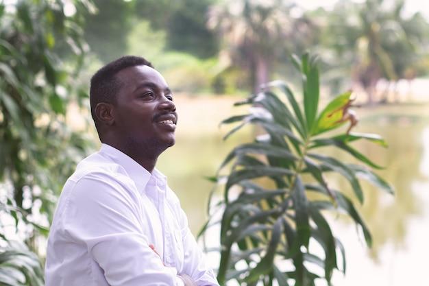 Uomo d'affari africano in camicia bianca guardando e pensando nel verde della natura