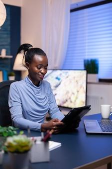 Donna d'affari africana che controlla la posta elettronica utilizzando un tablet pc la sera dall'ufficio di casa. impiegato concentrato e impegnato che utilizza la tecnologia moderna della rete wireless facendo gli straordinari.