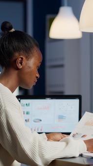 Donna d'affari africana in possesso di documenti con grafica