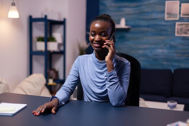 Donna d'affari africana che parla su smartphone che lavora a tarda notte dall'ufficio di casa. libero professionista concentrato che utilizza la moderna tecnologia di rete wireless facendo gli straordinari.