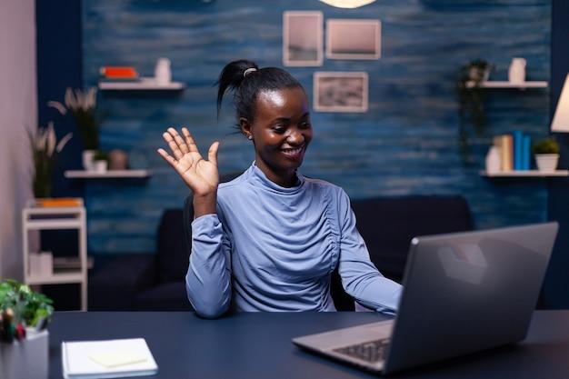Donna d'affari africana che saluta i clienti nel corso di una riunione virtuale seduta alla scrivania in ufficio a tarda notte. libero professionista nero che lavora con una conferenza virtuale online in chat di gruppo in remoto.