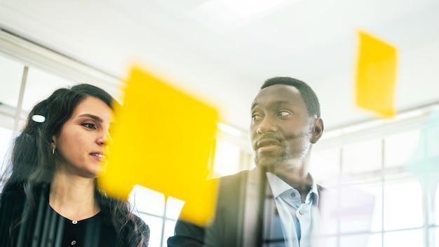 Uomo d'affari africano incontro di brainstorming con i colleghi utilizzando una nota di carta adesiva colorata sulla parete di vetro per trovare nuove idee. usare una metodologia agile e fare affari.
