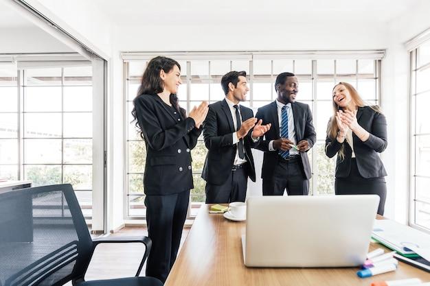 L'uomo d'affari africano conduce l'incontro, presenta il piano aziendale di successo con umore felice ei colleghi battono le mani.