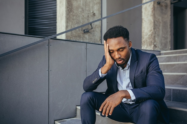 Uomo d'affari africano seduto frustrato sulle scale depresso dai risultati del suo lavoro, tenendosi per mano dietro la testa