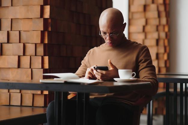 Uomo d'affari africano che parla al telefono seduto al tavolino del bar, imprenditore impegnato che lavora a distanza in una caffetteria con documenti per laptop che parlano al cellulare, uomo di colore che fa una chiamata pranzando in caffetteria