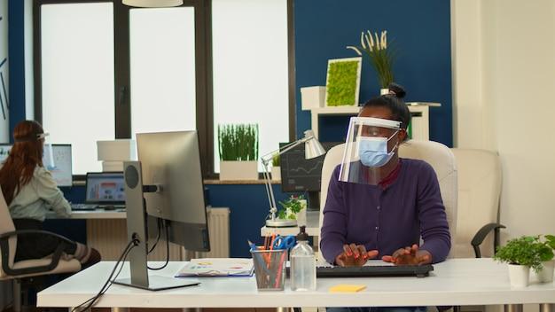 Donna d'affari africana che scrive rapporti sul computer in un occupato ufficio della società finanziaria aziendale che lavora con i cowerker rispettando la distanza sociale e indossando visiera e maschera protettiva.