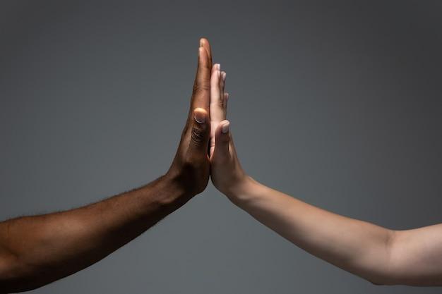 Mani africane e caucasiche che gesticolano su sfondo grigio studio