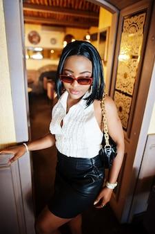 Ragazza afro chic con camicetta bianca e gonna di pelle nera. donna afroamericana alla moda.