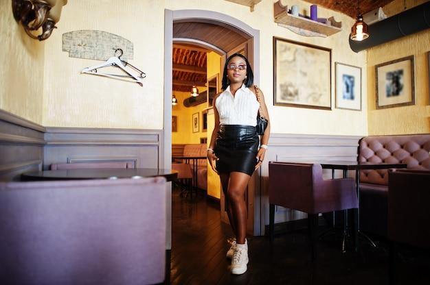 Ragazza afro chic con camicetta bianca, gonna in pelle nera e sneakers bianche. donna afroamericana alla moda.