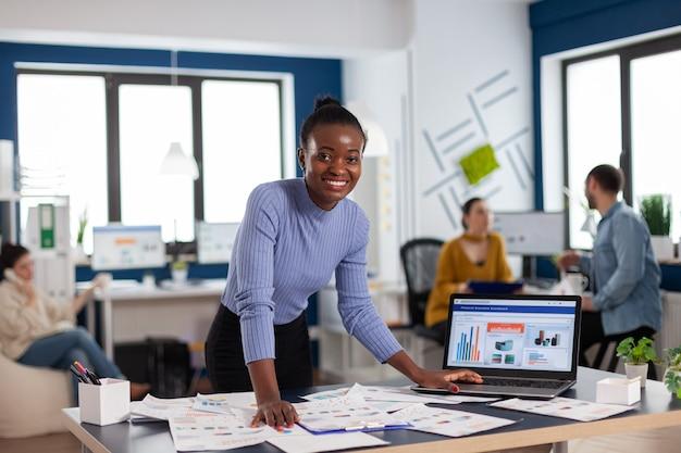 Leadership aziendale africana e imprenditore aziendale che guarda l'obbiettivo. diversi team di uomini d'affari che analizzano i rapporti finanziari dell'azienda dal computer.