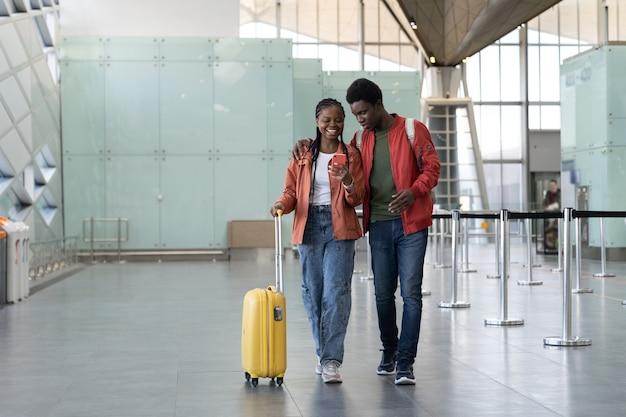 Coppia africana dopo l'arrivo in aereo cammina con i bagagli in aeroporto guardando lo smartphone