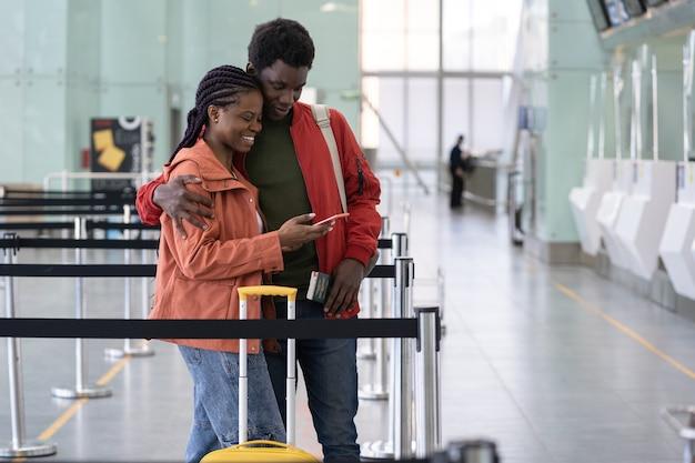 La coppia africana in aeroporto usa lo smartphone per il check-in online sul volo dopo la fine del viaggio in sicurezza covid