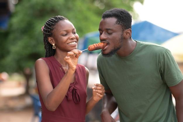 Coppia africana che mangia cibo da strada