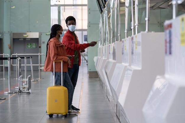 Coppia africana in maschera al check-in in aeroporto vuoto durante il blocco dell'epidemia di virus corona covid