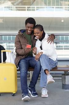 Coppia africana di turisti aspetta un taxi all'aeroporto ridendo da video divertenti su smartphone