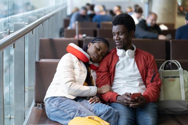La coppia africana di turisti nella zona di attesa del terminal dell'aeroporto si siede sul pisolino prima del check-in della partenza