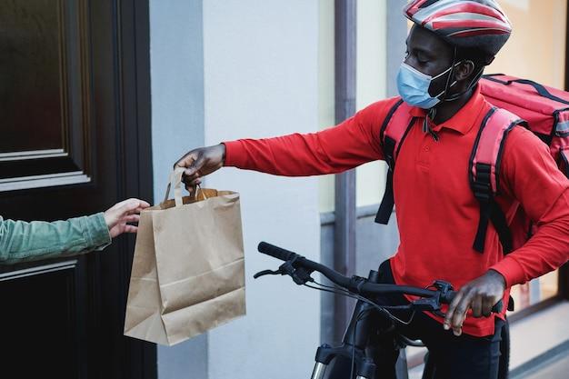 Uomo di corriere africano con zaino termico e bici che suona il campanello per il servizio di consegna - focus sul viso