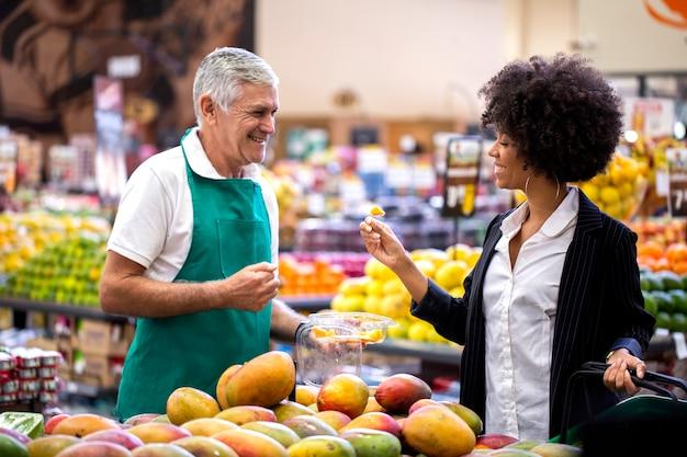 Cliente africano con fruttivendolo, tenendo il mango.