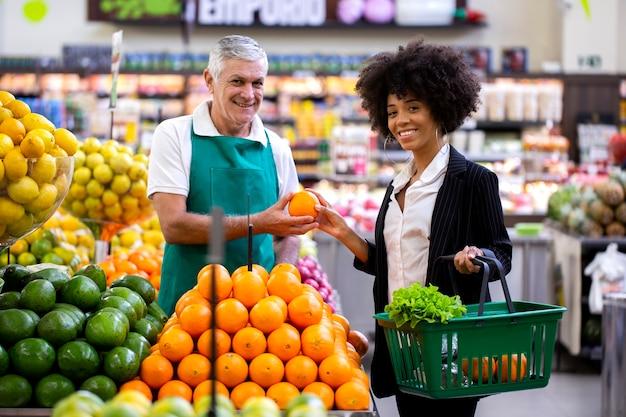Cliente africano con fruttivendolo, tenendo la frutta arancione.