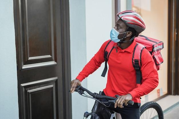 Fattorino africano con bici elettrica che suona il campanello durante il periodo del coronavirus - focus on face