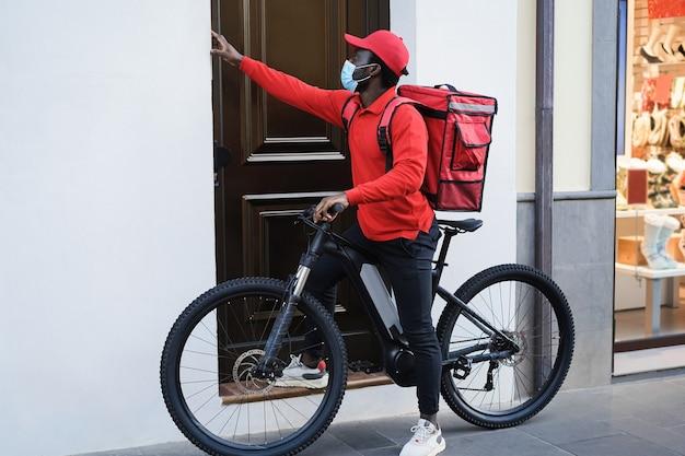 Uomo di consegna africano con bici elettrica che suona il campanello - focus sul viso