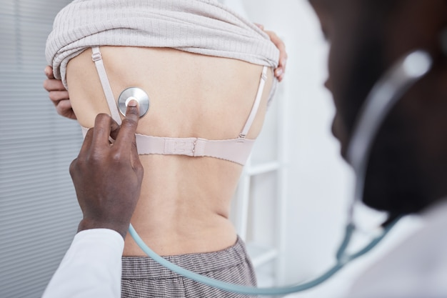 Medico africano che ascolta il battito cardiaco con lo stetoscopio al paziente all'ospedale