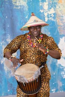Batterista africano in costume tradizionale giocando sul tamburo djembe