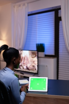 Imprenditore africano seduto alla scrivania in ufficio a casa tenendo tablet pc con schermo verde lavorando sulla scadenza. utilizzo del computer di visualizzazione della chiave di crominanza mockup.