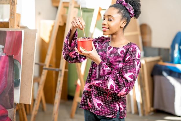 Studente di etnia africana con pennello in studio per dipingere