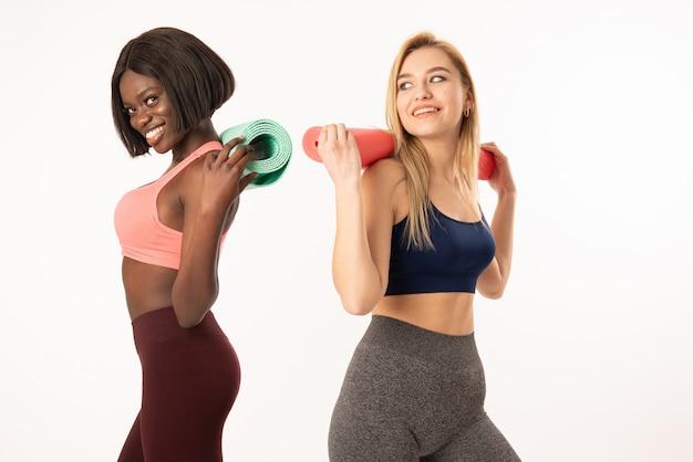 Ragazze sportive africane ed europee in abiti sportivi in piedi schiena contro schiena, ragazze internazionali