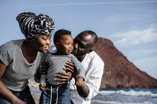Famiglia africana che gioca sulla spiaggia durante le vacanze estive - focus sulla faccia della madre - focus principale sulla faccia del bambino