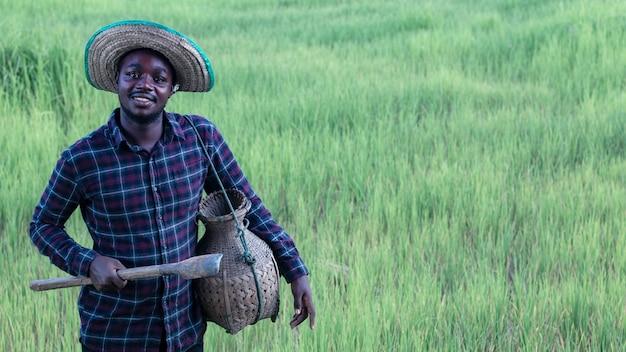 L'agricoltore africano sta lavorando felicemente nella sua fattoria con in mano strumenti agricoli. concetto di agricoltura o coltivazione
