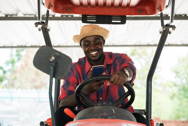 Agricoltore africano utilizza lo smartphone e guida il trattore in fattoria durante il raccolto in campagna. concetto di agricoltura o coltivazione