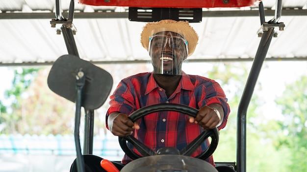 L'agricoltore africano indossa la protezione per il viso e guida il trattore in fattoria durante il raccolto in campagna. concetto di agricoltura o coltivazione