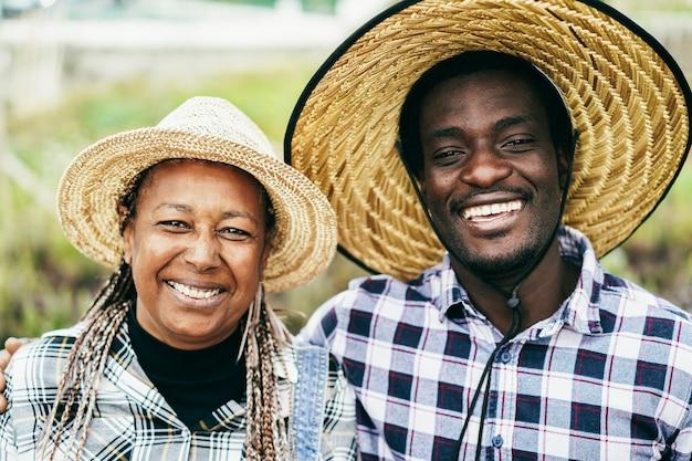 Smilion degli agricoltori africani sulla fotocamera durante il periodo del raccolto - concetto di stile di vita dell'azienda agricola - focus principale sui volti