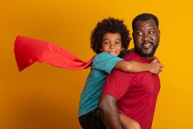 Padre e figlio africani che giocano il supereroe al tempo di giorno. persone che si divertono muro giallo. concetto di famiglia amichevole.