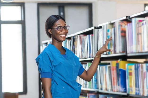 Donna africana che cerca felicemente un libro in biblioteca