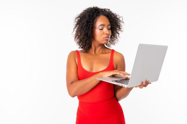 La femmina africana lavora con il computer portatile, immagine isolata sulla parete bianca