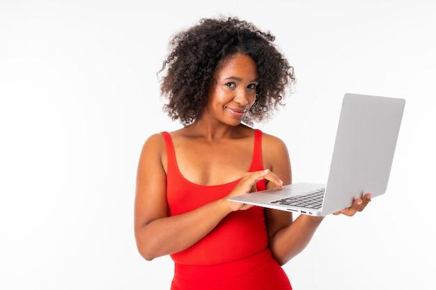 La femmina africana lavora con il computer portatile e i sorrisi, immagine isolata sulla parete bianca