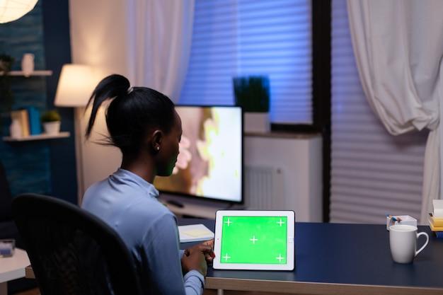 Donna africana freelance che si diverte a lavorare da casa guardando un tablet pc con copia spazio disponibile seduto alla scrivania. utilizzo del computer di visualizzazione della chiave di crominanza mockup.