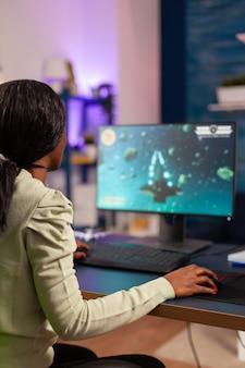 Giocatore africano che cerca di rilassarsi giocando al campionato online di sparatutto spaziale. la donna competitiva del giocatore informatico che esegue un torneo di videogiochi usa un joystick professionale.