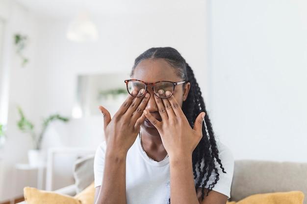 La ragazza africana con gli occhiali si strofina gli occhi, soffre di occhi stanchi, concetto di malattie oculari