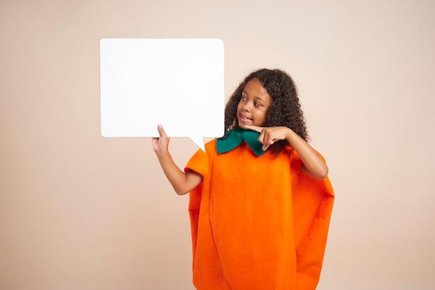 Ragazza africana in costume di halloween che tiene il fumetto vuoto