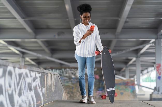 La pattinatrice africana con longboard tiene il telefono legge la notifica delle reti nello spazio per gli skateboarder
