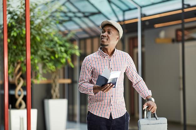 Ragazzo africano in possesso di passaporto e biglietti in piedi con la valigia in aeroporto che aspetta il suo volo