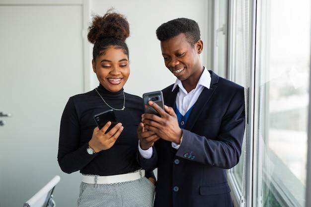 Bell'uomo africano e donna con i telefoni cellulari